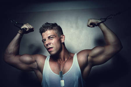 Portrait of a handsome strong guy trains his pecs using crossover