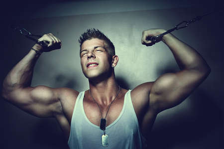 crossover: Portrait of a handsome strong guy trains his pecs using crossover