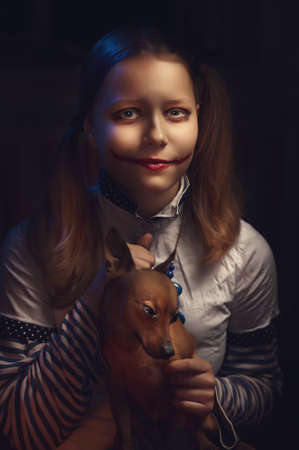 Clown teen girl with her puppy photo
