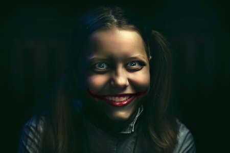 evil clown: Clown teen girl with a sinister smile Stock Photo