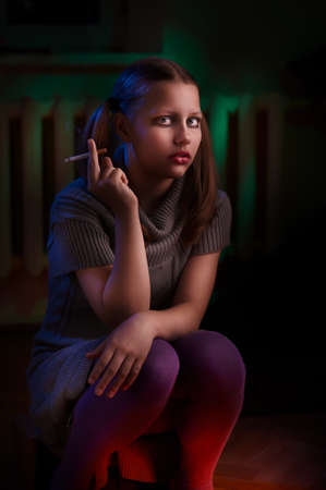 dysfunctional: Teen girl from a dysfunctional family sits and smokes Stock Photo