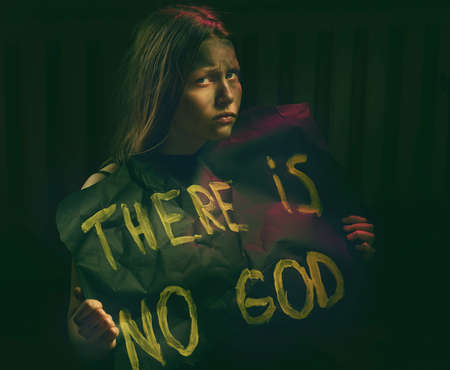 atheism: Teen girl with dirty face holding banner with a text - There is no God. Atheistic concept.