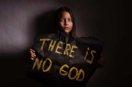 Atheist teen girl holding a banner with the inscription-THERE IS NO GOD
