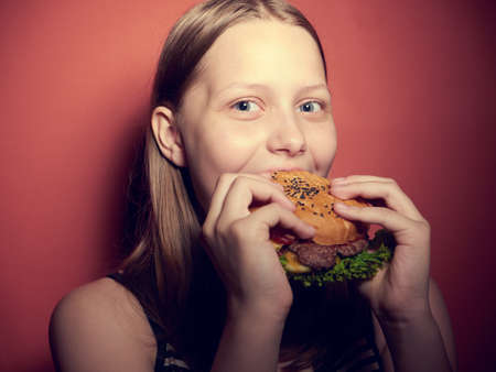 fat food: Teen girl with a delicious burger Stock Photo