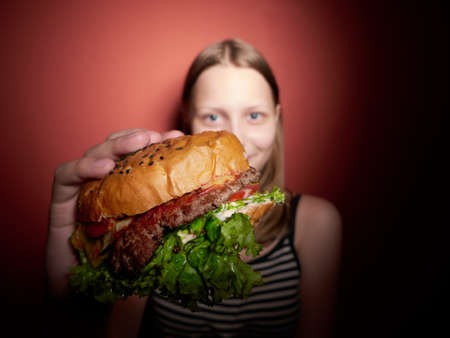 eating fast food: Teen girl with a delicious burger Stock Photo