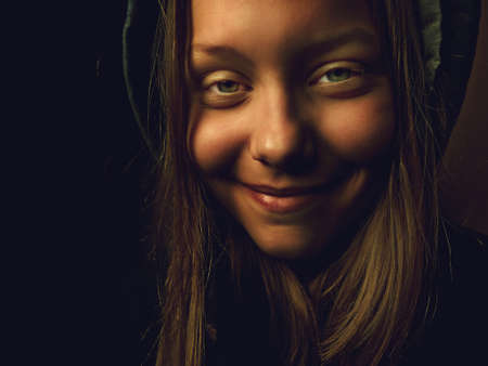 antichrist: Portrait of a devil teen girl with a sinister smile, closeup