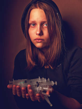 junkie: Portrait of a depressed teen girl, junkie with syringe. Pain and fear. Stock Photo