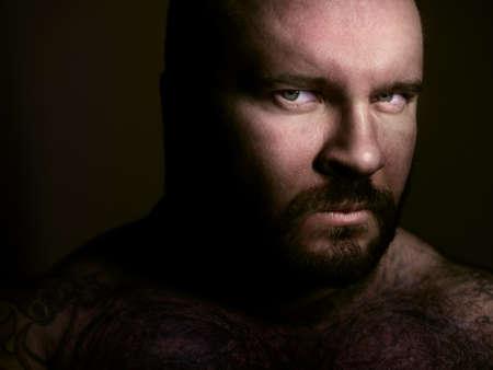 strong toughness: Dark closeup portrait of a bearded man