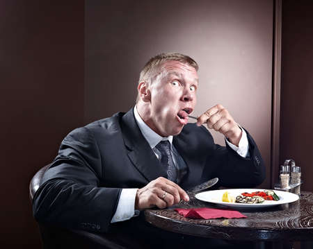 adult sandwich: Muscular businessman eating and lick the plate Stock Photo