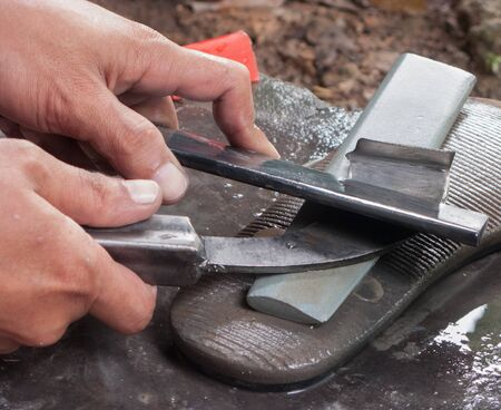 acuminate: Sharpen rubber tapping knife Stock Photo