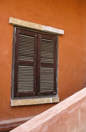 Old wood window on orange wall photo