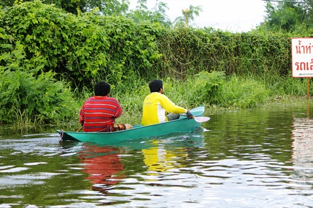 thailand flood: PATHUMTHANI, THAILAND - OCTOBER 16 : Unidentified people have to travel by boat on the road during flooding crisis, Pathumthani, Thailand on October 16, 2011.