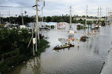 PATHUMTHANI, THAILAND - OCTOBER 16 : Unidentified people have to travel by boat on the road during flooding crisis, Pathumthani, Thailand on October 16, 2011.