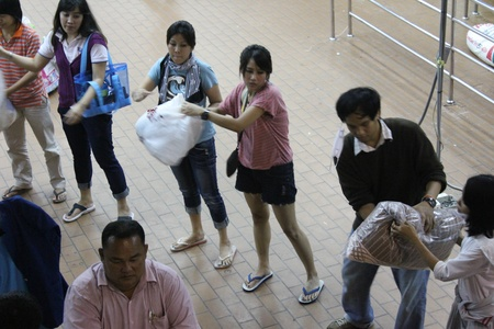 BANGKOK, THAILAND - OCTOBER 14 : Unidentified volunteers form themselves into human conveyor belt to transfer sacks of donated items due to the worst flood in Thailand on October 14, 2011 Don Mueang airport, Bangkok, Thailand