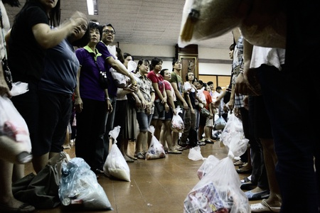 BANGKOK, THAILAND - OCTOBER 16 : Unidentified volunteers form themselves into human conveyor belt to transfer sacks of donated items due to the worst flood in Thailand on October 16, 2011 Don Mueang airport, Bangkok, Thailand
