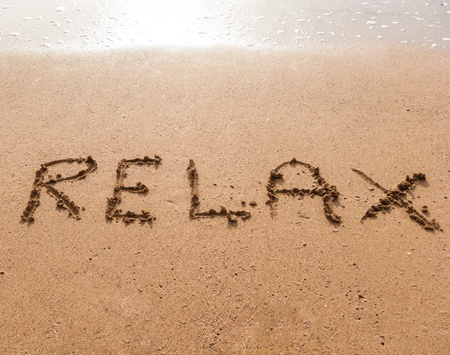 Word Relax in handwriting on sandy beach Stock Photo