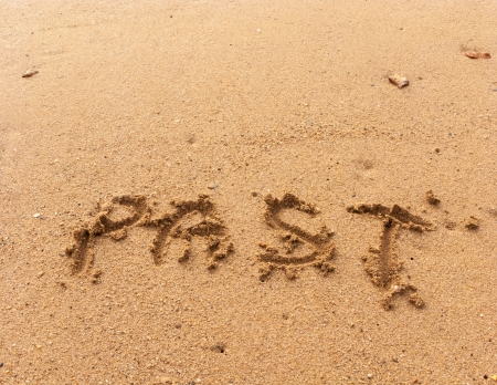 Word Past in handwriting on sandy beach photo