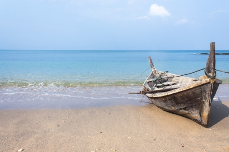 Long tail boat by the beach with blue sea and sky