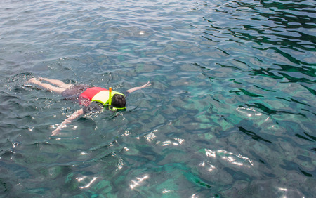 A man snorkeling in crystal turquoise sea water