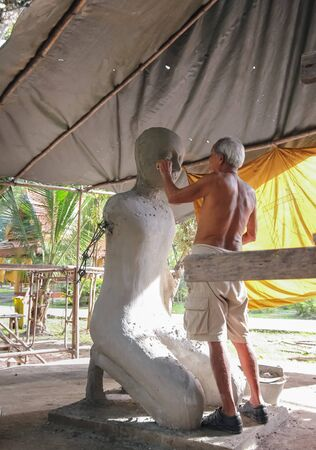 sculptor: CHANTHABURI, ThAILAND - December 16, 2012 : Elderly artist sculptor making monk sculpture at the temple