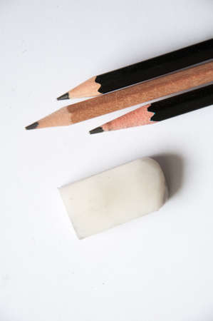three  pencil and one eraser on white background