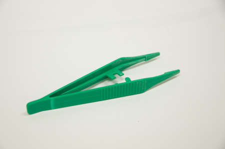 green plastic forceps isolated on white background photo