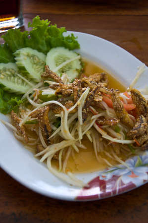 thai papaya salad hot and spicy mixed from variety of vegetable with fish fry photo
