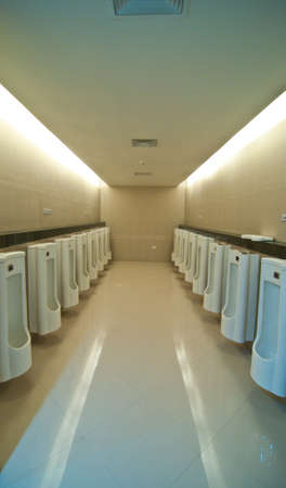 line of white automatic porcelain urinals in public toilets photo