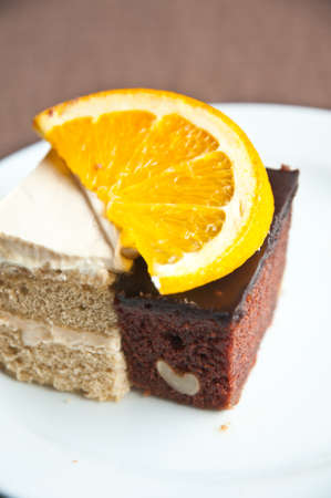 Chocolate and vanilla cake  and slice of orance photo
