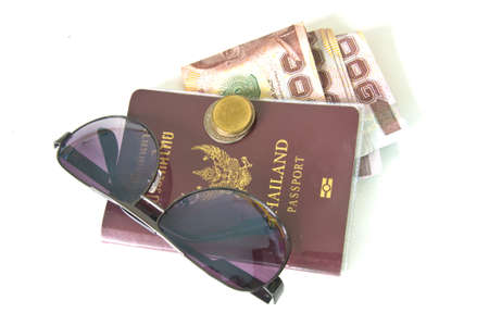 Thailand passport ,Sunglasses and Thai money on white background photo