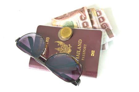 Thailand passport ,Sunglasses and Thai money on white background photo