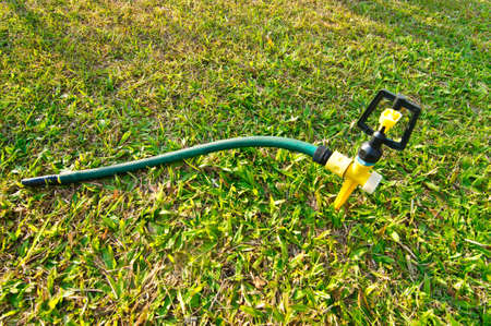 spattering: metal automatic water sprinkler in the garden Stock Photo