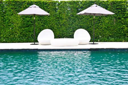 豪華游泳池與白色的時尚躺椅 版權商用圖片