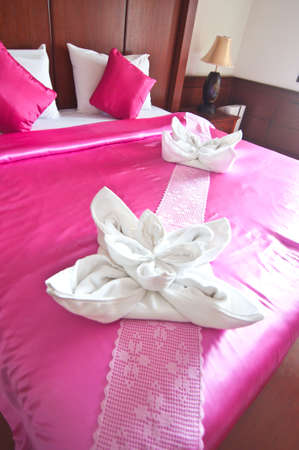 room in a hotel with a decoration of the towel  flowers on the bed