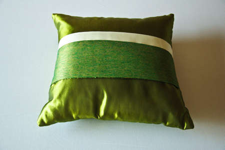green silk bright pillow on bed photo