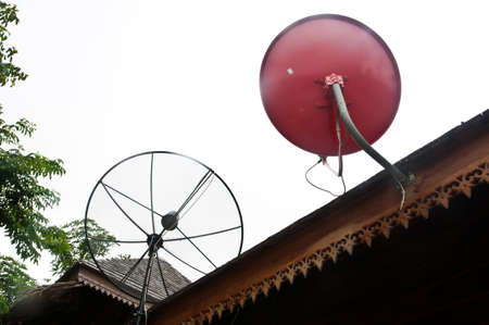 parabolic mirror: red Satellite dish on roof Stock Photo