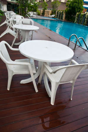 Table with chairs standing against the swimming pool Stock Photo - 22625426