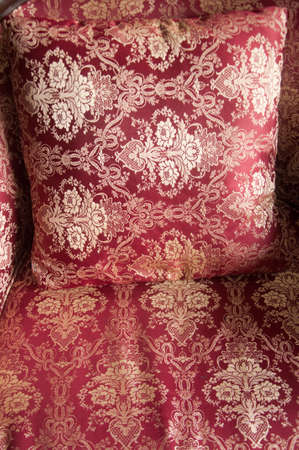luxurious cushions on bed in gold brocade, red textiles photo