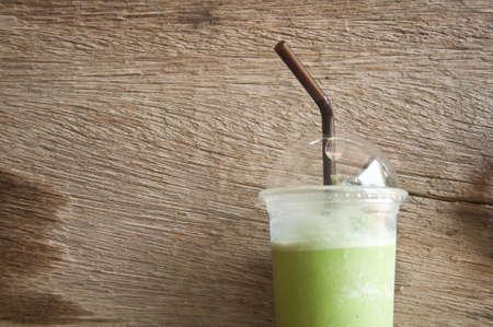 牛奶綠茶冰沙的塑料杯木材的背景 版權商用圖片