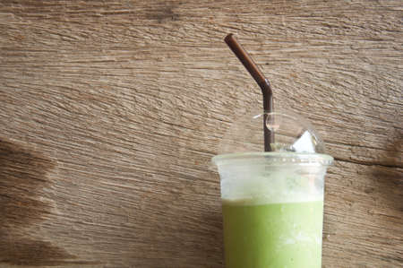matcha: milk green tea smoothie in plastic cup wood background