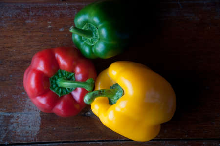 bell peppers: set of colored bell peppers on wood