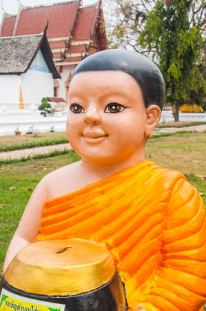 begging: monk baked clay doll with a begging bowl Stock Photo