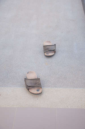 fulfill: pair old slippers on cement ground