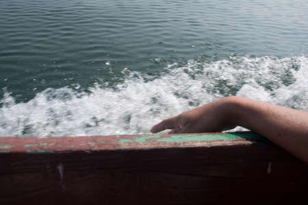 Een hand steken in het water tijdens een boottocht