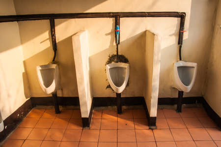 unsightly: row of dirty urinals in a public restroom