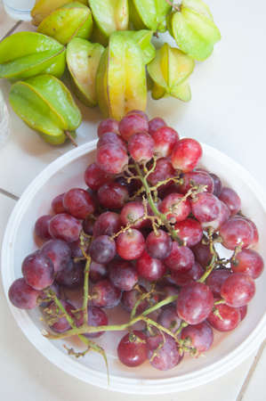 scurvy: Red grape berries and Star apple in white plate