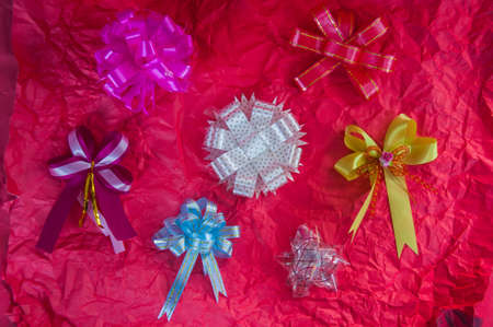 top veiw: set of colorful gift bows on red wrinkled paper Stock Photo