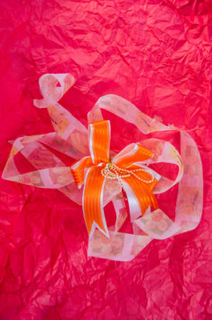 top veiw: ribbon bow on red wrinkled paper texture
