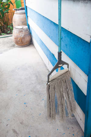 mops: dirty old mops against blue  wood wall