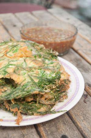cha om: Fried acacia pennata omelet or cha-om egg on wood table